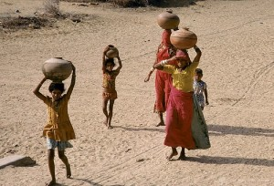 """Women and children carry water"""" by World Bank Photo Collection is licensed under CC BY-NC-ND 2.0"""